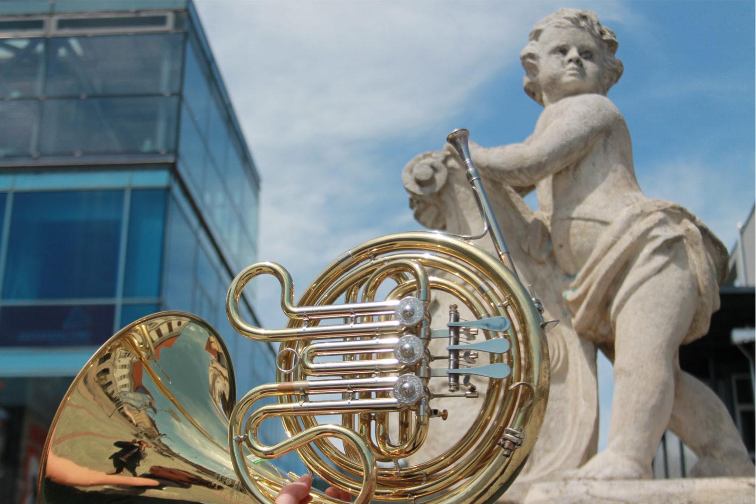Engelsbrunnen am Hauptplatz Leoben und Musikinstrument Horn